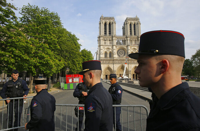 Members of Paris Firefighters' brigade enter the security perimeter to Notre Dame cathedral Thursday, April 18, 2019 in Paris. France paid a daylong tribute Thursday to the Paris firefighters who saved Notre Dame Cathedral from collapse, while construction workers rushed to secure an area above one of the church's famed rose-shaped windows and other vulnerable sections of the fire-damaged landmark. (AP Photo/Michel Euler, Pool)