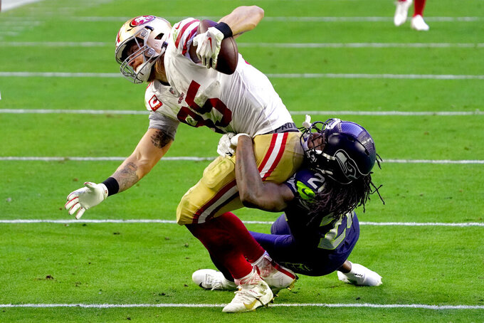 San Francisco 49ers tight end George Kittle (85) is tackled by Seattle Seahawks safety Ugo Amadi (28) during the second half of an NFL football game, Sunday, Jan. 3, 2021, in Glendale, Ariz. (AP Photo/Rick Scuteri)