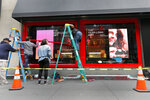 FILE - In this Tuesday, Nov. 5, 2019 file photo workers trim windows for the upcoming holiday season at the Macy's flagship store in New York.  Macy's cut its profit and sales expectations for the year after posting its first comparable store sales decline in almost two years, Thursday, Nov. 21. The company is citing the late arrival of colder weather, meager tourist business, weak traffic at some malls and problems on its website.  (AP Photo/Richard Drew, File)