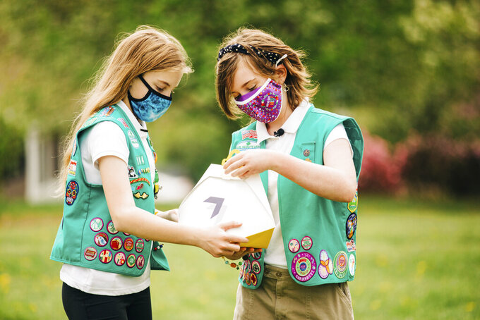 In this April 14, 2021 image provided by Wing LLC., from left, Girl Scouts, Alice and Gracie pose with a Wing delivery drone container in Christiansburg, Va. The company is testing drone delivery of Girl Scout cookies in the area. (Sam Dean/ Wing LLC. via AP)