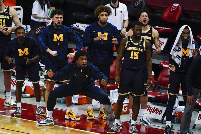 The Michigan bench react during the second half of an NCAA college basketball game against Wisconsin Sunday, Feb. 14, 2021, in Madison, Wis. (AP Photo/Morry Gash)
