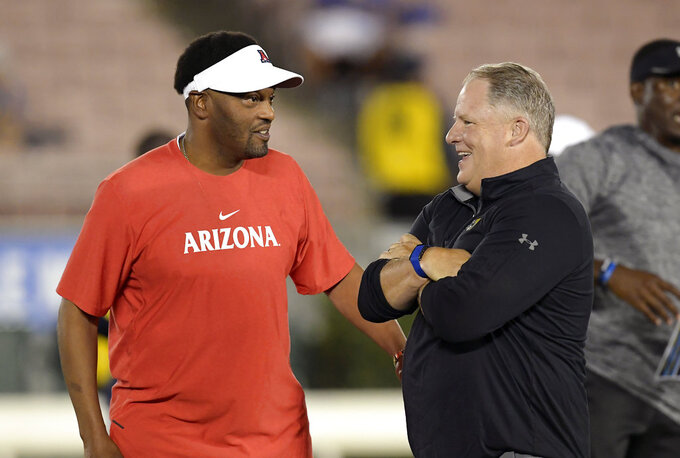 Arizona head coach Kevin Sumlin, left, talks with UCLA head coach Chip Kelly prior to an NCAA college football game, Saturday, Oct. 20, 2018, in Pasadena, Calif. (AP Photo/Mark J. Terrill)