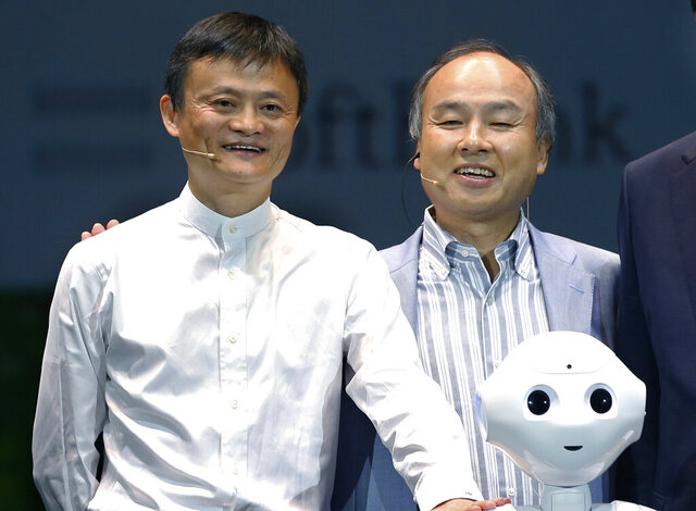 FILE - In this June 18, 2015, file photo, Softbank Corp. CEO Masayoshi Son, right, Alibaba Group Executive Chairman Jack Ma, left, of China with Foxconn Chairman and CEO Terry Gou of Taiwan pose for photographers with Softbank's Pepper robot during a press conference in Maihama, near Tokyo. Son, the chief executive of Japanese technology company SoftBank Group Corp. said Thursday, June 25, 2020, that he is stepping down from the board of Chinese e-commerce giant Alibaba. (AP Photo/Shizuo Kambayashi)