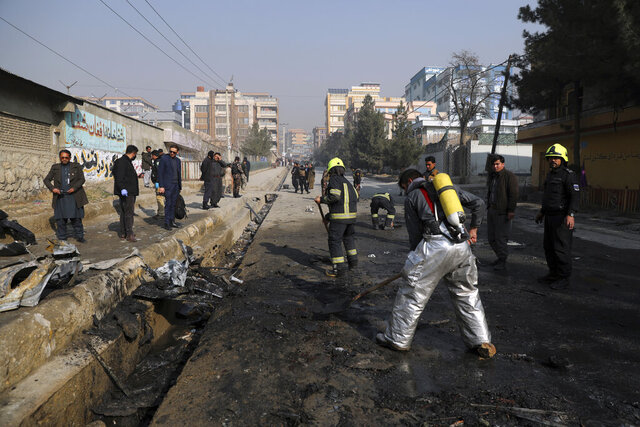 Afghan firefighters work at the site of a bombingh attack in Kabul, Afghanistan, Sunday, Jan. 10, 2021. A roadside bomb exploded in Afghanistan's capital Sunday, killing at least a few people in a vehicle, the latest attack to take place even as government negotiators are in Qatar to resume peace talks with the Taliban. (AP Photo/Rahmat Gul)