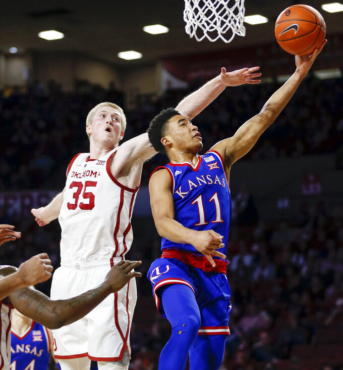 Kansas guard Devon Dotson (11) shoots in front of Oklahoma forward Brady Manek (35) in the first half of an NCAA college basketball game in Norman, Okla., Tuesday, March 5, 2019. (AP Photo/Nate Billings)