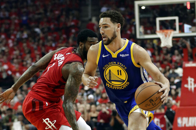 FILE- In this May 10, 2019, file photo, Golden State Warriors' Klay Thompson (11) drives past Houston Rockets' Iman Shumpert during the first half of Game 6 of a second-round NBA basketball playoff series in Houston. The Warriors said Thursday, Nov. 19, 2020, that Thompson has suffered a torn right Achilles tendon and is expected to miss the upcoming season.  Thompson was injured during a pickup game in Southern California the day before.  (AP Photo/Eric Gay, File)