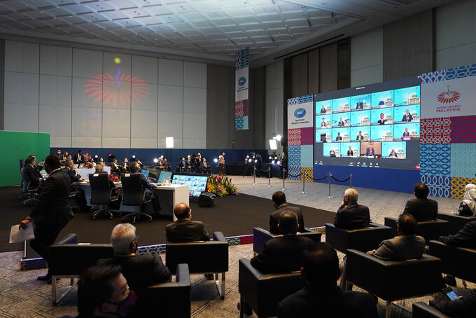 Malaysia's Prime Minister Muhyiddin Yassin, table at left, attend the opening remarks of the first virtual Asia-Pacific Economic Cooperation (APEC) leaders' summit, hosted by Malaysia, in Kuala Lumpur, Malaysia, Friday, Nov. 20, 2020. (AP Photo/Vincent Thian)