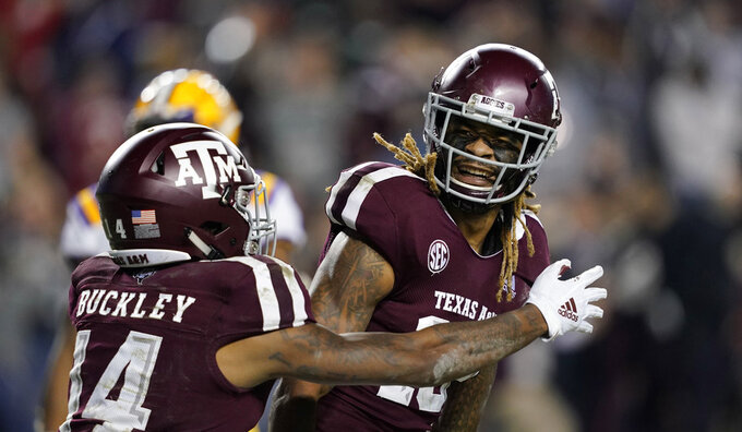 Texas A&M wide receiver Kendrick Rogers, right, celebrates with Camron Buckley (14) after catching a pass for a two-point conversion during the seventh overtime of an NCAA college football game against LSU Saturday, Nov. 24, 2018, in College Station, Texas. Texas A&M won 74-72. (AP Photo/David J. Phillip)