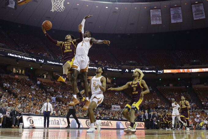 Central Michigan's Romelo Burrell (24) drives to basket Texas' Andrew Jones' defends during the first half of an NCAA college basketball game, Saturday, Dec. 14, 2019, in Austin, Texas. (AP Photo/Eric Gay)