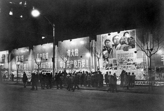 """FILE - In this Jan. 6. 1967 file photo, citizens crowd in front of illuminated bulletin boards to read newspapers on a wall along Nanking street in Shanghai, China. Posters above read, """"Long Live the Cultural Revolution, Long Live the Chinese People, Long Live the Great Chinese Communist Party."""" Chairman Mao's Cultural Revolution from the mid-1960s caused the deaths of up to two million people and affected all parts of society. It was seen as an attack to rid the country of his enemies which subsequent leaders described as a catastrophe period that set the nation back years. (AP Photo)"""