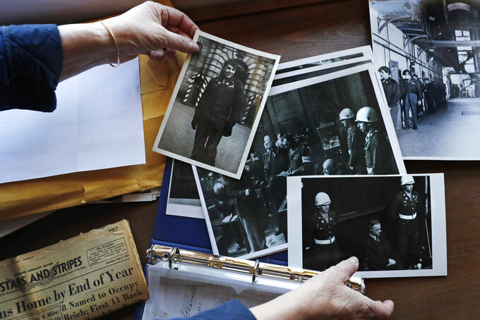 FILE - In this May 13, 2020 file photo, Emily DiPalma Aho looks over photographs and memorabilia of her father, Emilio DiPalma, a World War II veteran, at her home in Jaffrey, N.H. Emilio, who as a 19-year-old U.S. Army infantryman stood guard at the Nuremberg Nazi war crimes trials, died last month at the age of 93 after contracting the coronavirus at Holyoke Soldiers' Home in Massachusetts. The passage of a milestone — 100,000 lives lost due to the coronavirus in the United States — has brought attention to how news organizations are trying to tell the stories behind the numbers. (AP Photo/Charles Krupa, File)