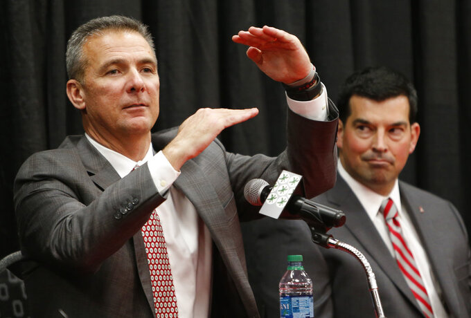 Ohio State NCAA college football head coach coach Urban Meyer, left, answers questions during a news conference announcing his retirement Tuesday, Dec. 4, 2018, in Columbus, Ohio. At right is assistant coach Ryan Day. (AP Photo/Jay LaPrete)