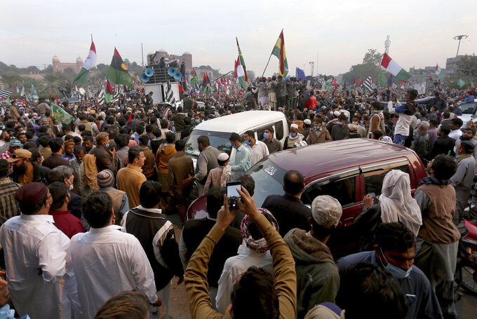 Supporters of the Pakistan Democratic Movement, an alliance of opposition parties, attend an anti-government rally, in Multan, Pakistan, Monday, Nov. 30, 2020. Despite a government ban and arrests of hundreds of activists, Pakistani opposition supporters rallied in a central city on Monday, calling on Prime Minister Imran Khan to resign over alleged bad governance and incompetence. (AP Photo/Asim Tanveer)