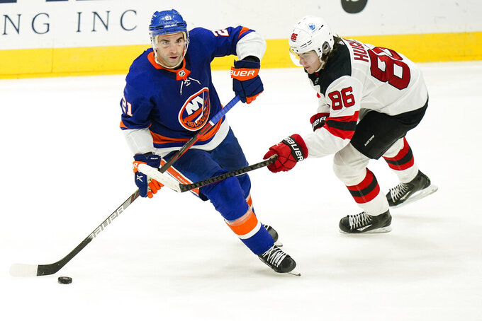 New Jersey Devils' Jack Hughes (86) fights for control of the puck with New York Islanders' Kyle Palmieri (21) during the third period of an NHL hockey game Saturday, May 8, 2021, in Uniondale, N.Y. The Islanders won 5-1. (AP Photo/Frank Franklin II)