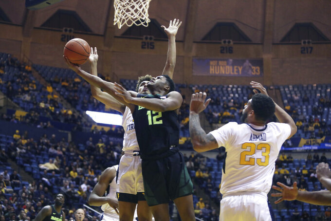 Baylor guard Jared Butler (12) shoots while defended by West Virginia forward Emmitt Matthews Jr. (11) during the first half of an NCAA college basketball game Monday, Jan. 21, 2019, in Morgantown, W.Va. (AP Photo/Raymond Thompson)