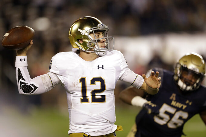 Notre Dame quarterback Ian Book (12) prepares to throw a pass under pressure from Navy linebacker Nizaire Cromartie during the second half of an NCAA college football game Saturday, Oct. 27, 2018, in San Diego. (AP Photo/Gregory Bull)
