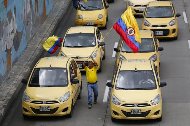 FILE- In this May 10, 2017 file photo, taxi drivers strike to pressure the government to ban the ride-sharing app Uber, in Bogota, Colombia. Uber says on Friday, Jan. 10, 2020 it will stop operating in Colombia following stiff opposition from taxi drivers' unions and a lawsuit that said the ride-sharing app was breaking local transport laws. (AP Photo/Fernando Vergara, File)