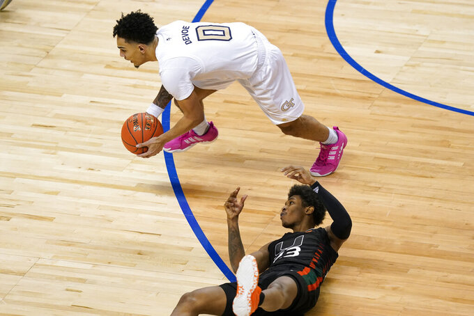 Georgia Tech guard Michael Devoe (0) grabs the ball from Miami guard Kameron McGusty (23) during the second half of an NCAA college basketball game in the quarterfinal round of the Atlantic Coast Conference tournament in Greensboro, N.C., Thursday, March 11, 2021. (AP Photo/Gerry Broome)