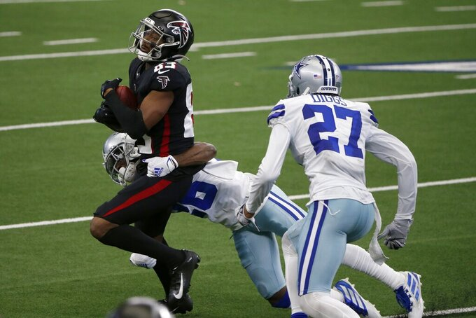 Atlanta Falcons wide receiver Russell Gage (83) is stopped after making a catch by Dallas Cowboys' Jourdan Lewis, rear, and Trevon Diggs (27) in the second half of an NFL football game in Arlington, Texas, Sunday, Sept. 20, 2020. (AP Photo/Michael Ainsworth)