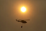 A helicopter flies over a wildfire in Estepona, Spain, Thursday, Sept. 9, 2021. Nearly 800 people have been evacuated from their homes and road traffic has been disrupted as firefighting teams and planes fight a wildfire in southwestern Spain. (AP Photo/Sergio Rodrigo)
