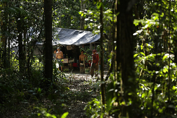 Illegal loggers stand in their camp as Tenetehara Indigenous men from the Ka'Azar, or Forest Owners, approach them and surround them on their lands on the Alto Rio Guama reserve in Para state, near the city of Paragominas, Brazil, Tuesday, Sept. 8, 2020. Three Tenetehara Indigenous villages are patrolling to guard against illegal logging, gold mining, ranching, and farming on their lands, as increasing encroachment and lax government enforcement during COVID-19 have forced the tribe to take matters into their own hands. (AP Photo/Eraldo Peres)