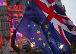FILE - In this file photo dated Thursday, Jan. 30, 2020, a woman holds up the British Union and the European Union flags together during an event in Brussels, Belgium. The number of Britons moving to live in European Union countries has soared since the Brexit vote in 2016, a U.K.-German study has revealed Tuesday Aug. 4, 2020. (AP Photo/Francisco Seco, FILE)