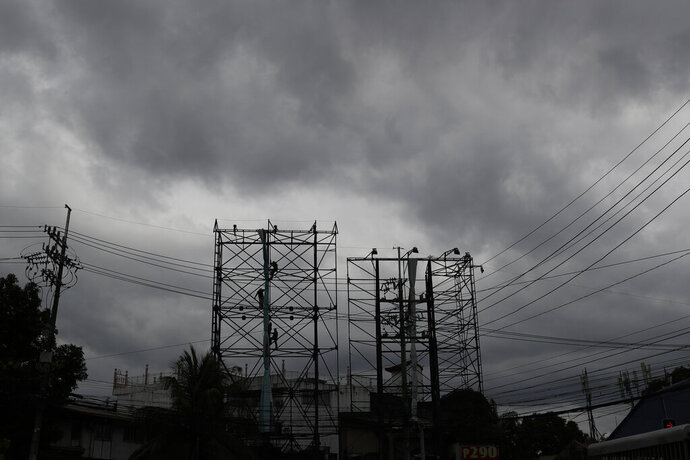 Dark clouds envelop the skies as workers fold a billboard to prepare for the coming of typhoon Vongfong in Manila, Philippines Thursday May, 14, 2020. The first typhoon to hit the country this year roared toward the eastern Philippines on Thursday as authorities work to evacuate tens of thousands of people while avoiding overcrowding in shelters that could spread the coronavirus. (AP Photo/Aaron Favila)