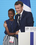 France's President Emmanuel Macron, right, poses with goodwill ambassador of the ONG