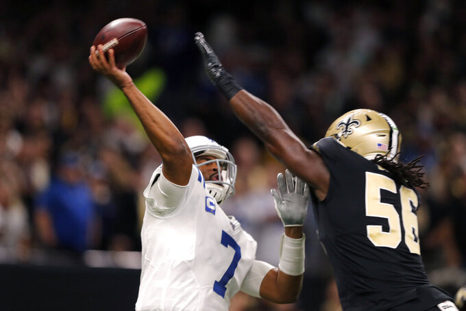 Indianapolis Colts quarterback Jacoby Brissett (7) passes under pressure from New Orleans Saints outside linebacker Demario Davis in the first half of an NFL football game in New Orleans, Monday, Dec. 16, 2019. (AP Photo/Gerald Herbert)