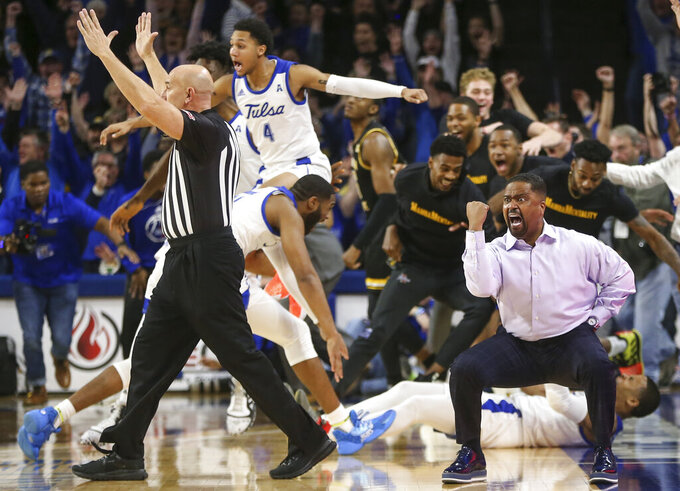 Tulsa coach Frank Haith, right, reacts after Tulsa guard Elijah Joiner, behind Haith on floor, hit a three-pointer at the buzzer to beat  Wichita State 54-51 in an NCAA college basketball game, Saturday, Feb. 1, 2020 in Tulsa, Okla. (Travis Heying/The Wichita Eagle via AP)