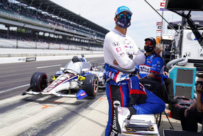 Graham Rahal waits next to his car in the opening 30 minutes of practice for the Indianapolis 500 auto race at Indianapolis Motor Speedway in Indianapolis, Friday, May 21, 2021. IndyCar has punished Rahal Letterman Lanigan for trying to stage a photo in the opening minutes of Thursday's practice and were force to sit out the first 30 minutes of practice on Friday. (AP Photo/Michael Conroy)