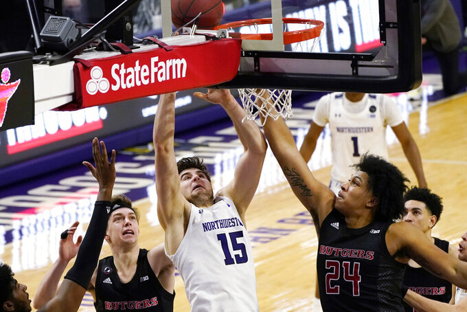 Northwestern center Ryan Young, center, shoots against Rutgers guard Paul Mulcahy, left, and guard/forward Ron Harper Jr., during the second half of an NCAA college basketball game in Evanston, Ill., Sunday, Jan. 31, 2021. (AP Photo/Nam Y. Huh)