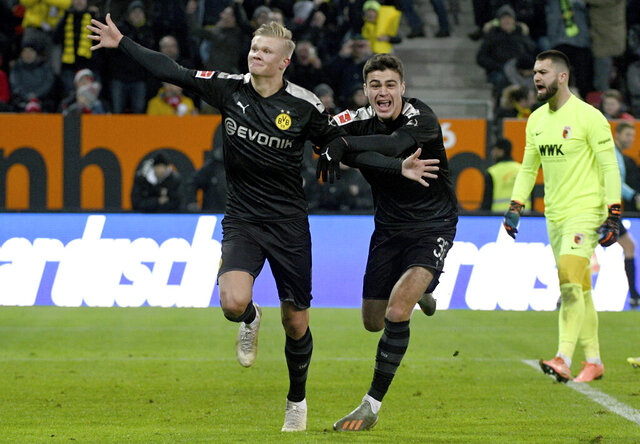 Dortmund's Erling Haaland, left, celebrates with Giovanni Reyna after scoring a goal in a German Bundesliga soccer match between FC Augsburg and Borussia Dortmund in Augsburg, Germany, Saturday, Jan.18, 2020. ( Stefan Puchner/dpa via AP)