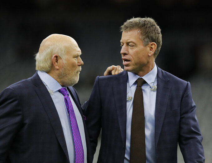 Former NFL quarterback Terry Bradshaw, left speaks with broadcaster and former NFL quarterback Troy Aikman before the NFL football NFC championship game between the New Orleans Saints and the Los Angeles Rams, Sunday, Jan. 20, 2019, in New Orleans. (AP Photo/Carolyn Kaster)