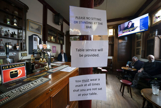 People sit in the Dispensary pub in Liverpool, England, Monday Oct 12, 2020. The British government has carved England into three tiers of risk in a bid to slow the spread of a resurgent coronavirus. The northern city of Liverpool is in the highest category and will close pubs, gyms and betting shops. (AP Photo/Jon Super)