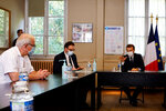 French President Emmanuel Macron, right, chairs a meeting with the medical staff of the Rene Dubos hospital center, in Pontoise, outside Paris, Friday Oct. 23, 2020. French Prime Minister Jean Castex said Thursday a vast extension of the nightly curfew that is intended to curb the spiraling spread of the coronavirus, saying