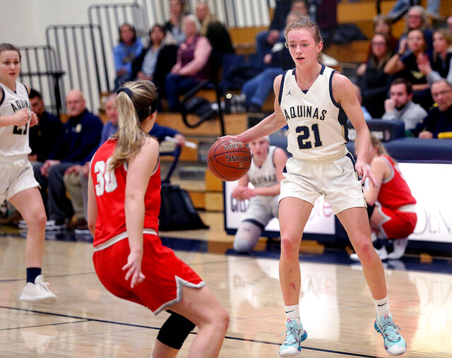 In this Jan. 21, 2020, photo, La Crosse Aquinas' Lexi Donarski is defended by a La Crosse Logan player during a high school basketball game in La Crosse, Wis. The Associated Press has selected Donarski as its girls basketball player of the year, and her father, Dave, as its coach of the year after a 25-1 season and 107-3 career with the Blugolds, who qualified for the past four WIAA Division 4 championship games and won two of the three they played. (Peter Thomson/La Crosse Tribune via AP)