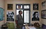 In this Nov. 6, 2019 photo, Sri Lankan media rights activist Udaya Kalupathirana stands in his office looking at posters of Sri Lankan journalists who had been allegedly tortured by groups of government soldiers during the last stages of president Mahinda Rajapaksa's regime in Colombo, Sri Lanka. Forced to flee their country a decade ago to escape allegedly state-sponsored killer squads, Sri Lankan journalists living in exile doubt they'll be able to return home soon or see justice served to their tormentors _ whose alleged ringleader could come to power in this weekend's presidential election. Exiled journalists and media rights groups are expressing disappointment over the current government's failure in punishing the culprits responsible for crimes committed against media members.  (AP Photo/Eranga Jayawardena)