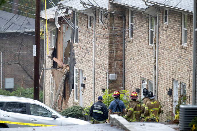 Fire officials look at the scene where an airplane crashed into an apartment complex, Wednesday, Oct. 30, 2019, in Atlanta. (AP Photo/David Goldman)