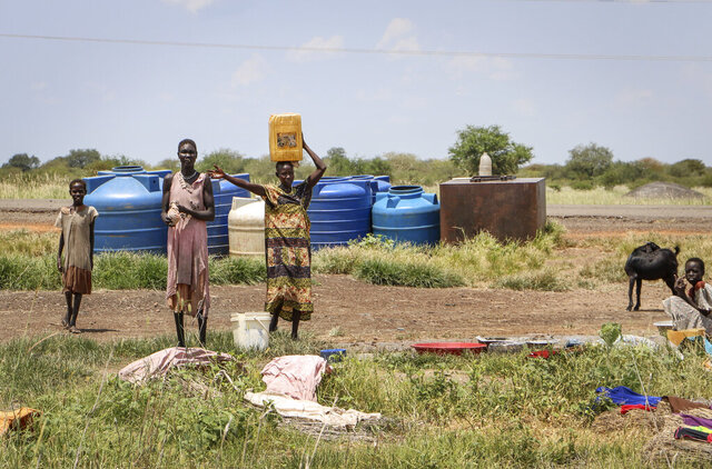 In this photo taken Monday, Oct. 1, 2018, residents stand by the side of the road after fetching water, between Melut and Paloch town, in South Sudan. The oil industry in South Sudan has left a landscape pocked with hundreds of open waste pits with the water and soil contaminated with toxic chemicals and heavy metals, and accounts of