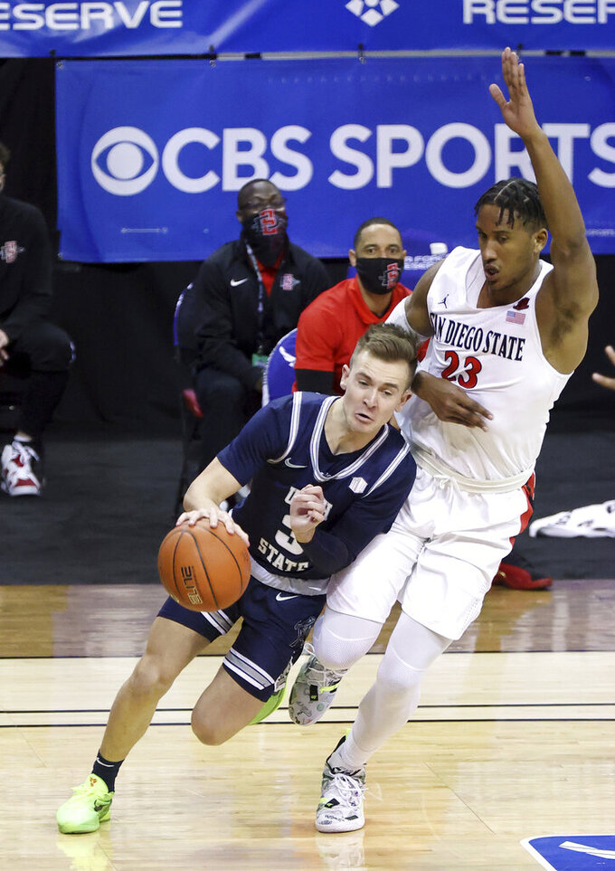 Utah State guard Steven Ashworth (3) drives as San Diego State forward Joshua Tomaic (23) defends during the first half of an NCAA college basketball game in the championship of the Mountain West Conference men's tournament Saturday, March 13, 2021, in Las Vegas. (AP Photo/Isaac Brekken)