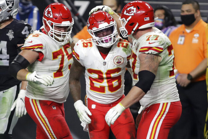 Kansas City Chiefs offensive tackle Mike Remmers, left, and offensive guard Andrew Wylie, right, celebrate after running back Le'Veon Bell (26) scored a touchdown against the Las Vegas Raiders during the second half of an NFL football game, Sunday, Nov. 22, 2020, in Las Vegas. (AP Photo/Isaac Brekken)