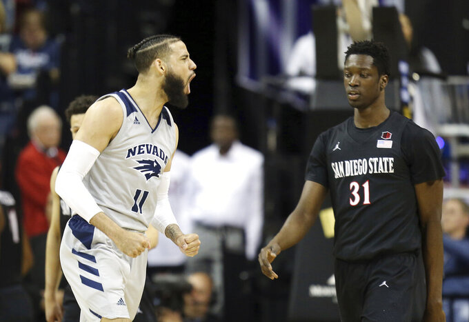 Nevada's Cody Martin (11) reacts after a basket as San Diego State's Nathan Mensah (31) walks past during the second half of an NCAA college basketball game in the Mountain West Conference men's tournament Friday, March 15, 2019, in Las Vegas. (AP Photo/Isaac Brekken)