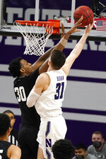 Michigan State forward Marcus Bingham Jr., left, blocks a shot by Northwestern forward Robbie Beran during the first half of an NCAA college basketball game in Evanston, Ill., Sunday, Dec. 20, 2020. (AP Photo/Nam Y. Huh)