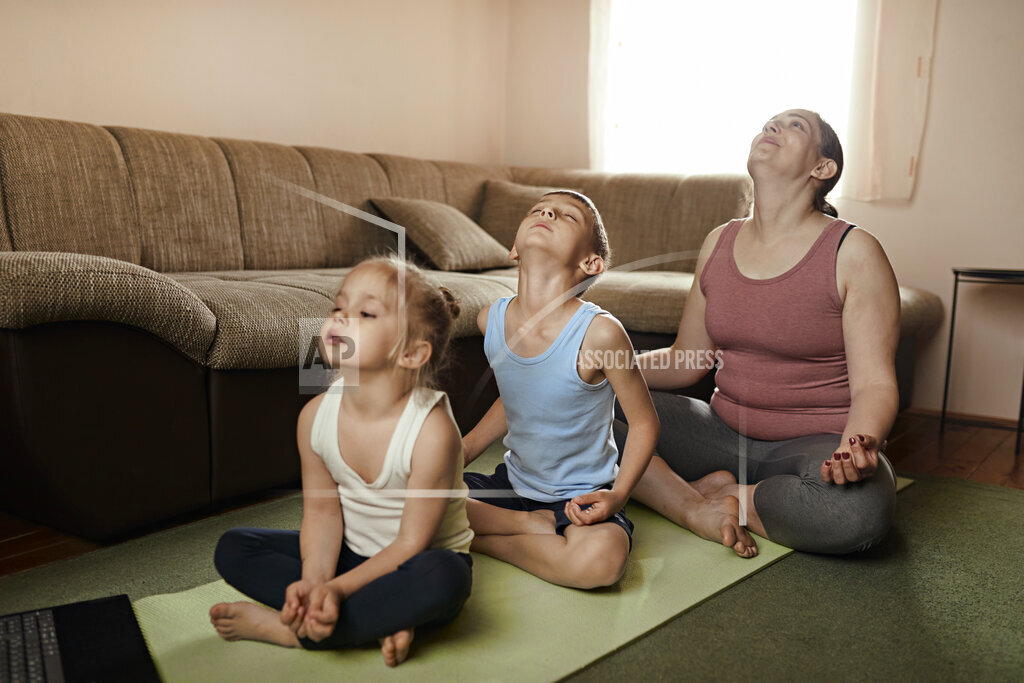 Son and daughter practicing yoga with mother at home