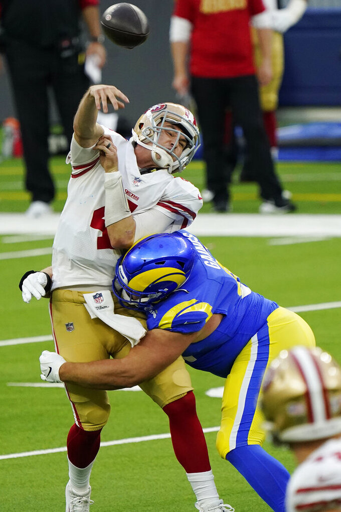 San Francisco 49ers quarterback Nick Mullens, left, is hit as he throws by Los Angeles Rams defensive tackle Greg Gaines during the second half of an NFL football game Sunday, Nov. 29, 2020, in Inglewood, Calif. (AP Photo/Alex Gallardo)