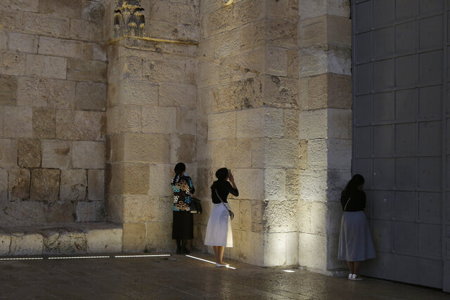 Jewish women pray at the Jaffa Gate to the Old City of Jerusalem, after they were turned away by police on their way to pray at the Western Wall, during a nationwide three-week lockdown to curb the spread of the coronavirus, Tuesday, Sept. 22, 2020,. (AP Photo/Maya Alleruzzo)
