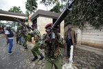 FILE - In this Tuesday, Jan. 15, 2019 file photo, Kenyan security forces aim their weapons up at buildings as they run through a hotel complex during an attack by extremists in Nairobi, Kenya. These African stories captured the world's attention in 2019 - and look to influence events on the continent in 2020. (AP Photo/Ben Curtis, File)