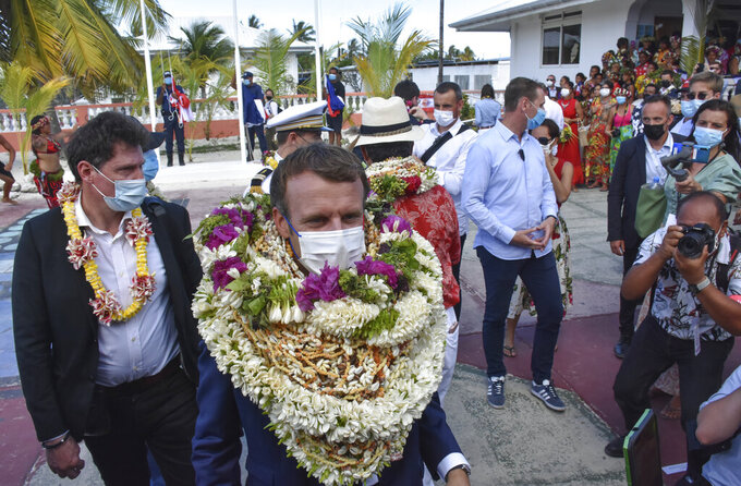 """France's President Emmanuel Macron wears a flowers leis and seashell necklaces as he arrived at the Manihi Atoll, 500 kms (312 mls) north east of Tahiti, French Polynesia in the Pacific Ocean, Monday, July 26, 2021.  On Friday, July 30, The Associated Press reported on stories circulating online incorrectly claiming a video shows Macron becoming a """"human wreath"""" during his official welcome to French Polynesia, when in fact the video was manipulated to add additional leis. (AP Photo/Esther Cuneo, File)"""