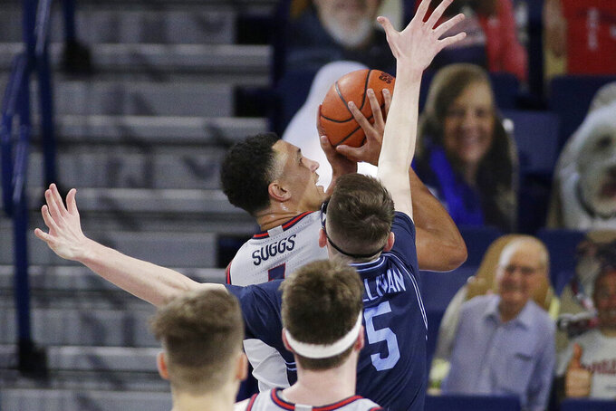 Gonzaga guard Jalen Suggs, left, shoots while pressured by San Diego guard Finn Sullivan during the first half of an NCAA college basketball game in Spokane, Wash., Saturday, Feb. 20, 2021. (AP Photo/Young Kwak)